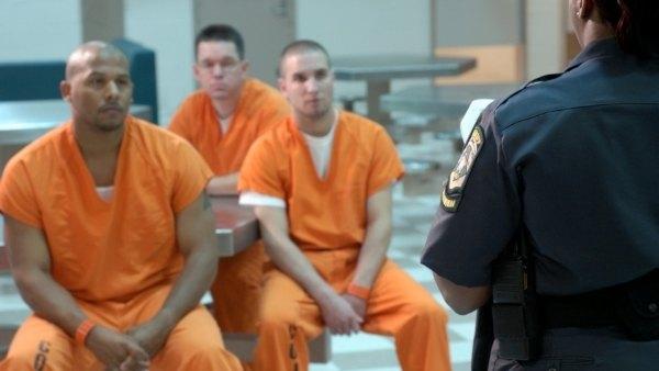 Bilde av tre fanger som skal til å utsette en fengselsbetjent for vold